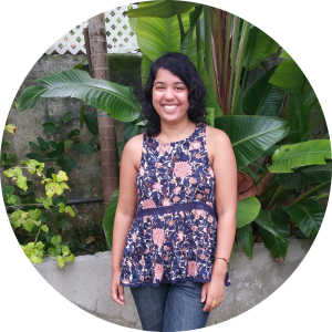 [Photo of the author, Asha Mattai, in front of tropical plants. She is smiling.]