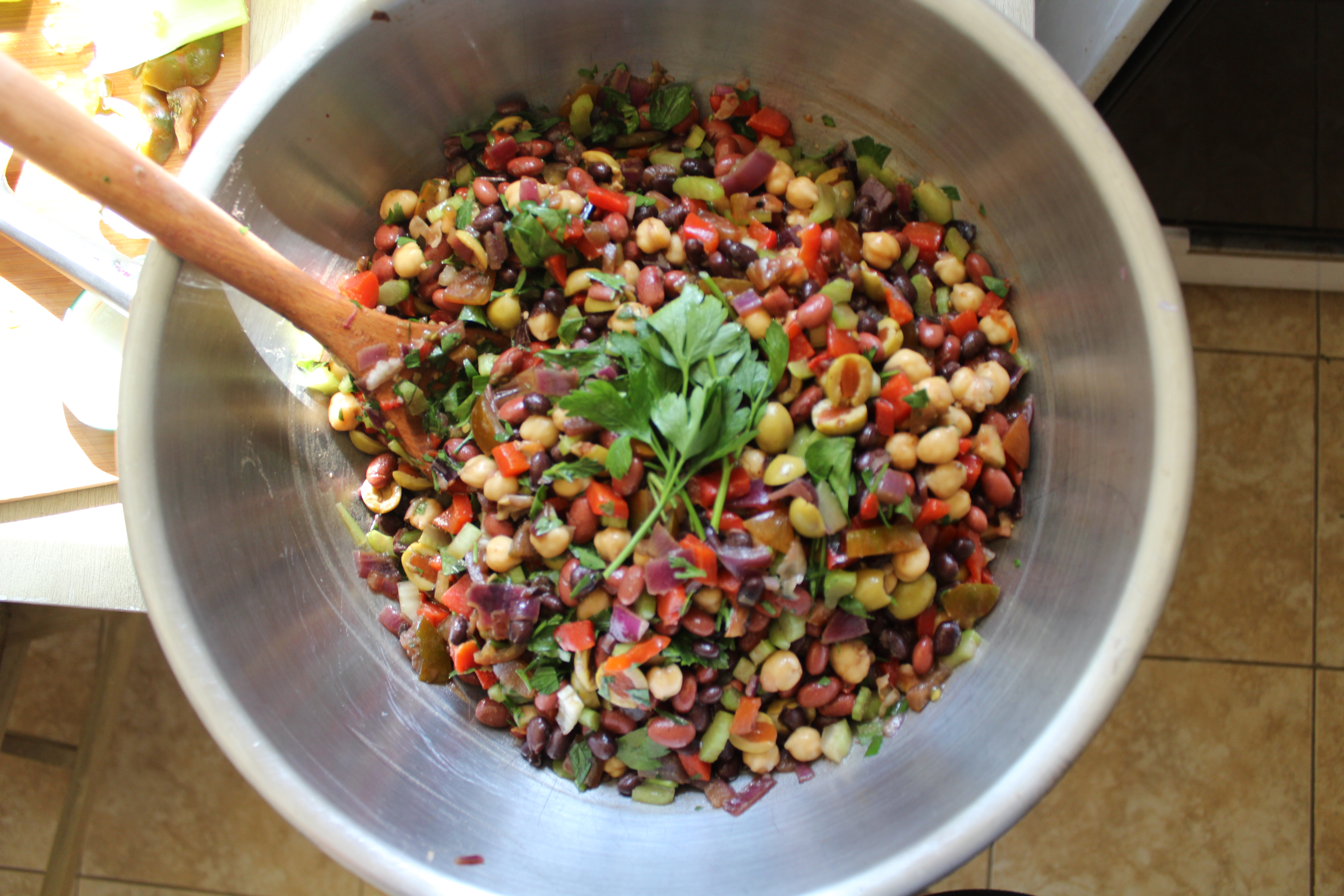 [Looking directly down into a large bowl of colorful mixed beans and chopped vegetables.]